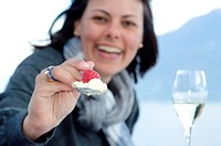 Woman giving raspberry and ice cream with a spoon