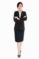 Woman in black suit with folded arms against white background