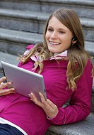 Beautiful young Caucasian woman taking with a bluetooth headset while holding a digital tablet
