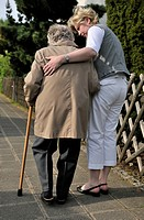 Senior woman walking with the help of a caregiver