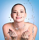 Happy young woman washing her face with clean water