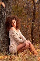 beautiful young woman sitting near a tree
