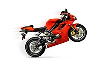 Red Triumph Daytona sport motorcycle doing a wheelie