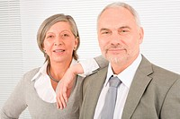 Professional elegant smiling senior businesswoman leaning against her male colleague