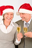 Laughing elegant senior businesspeople in Christmas hat drink champagne