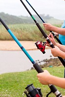 closeup of three people holding fishing rods