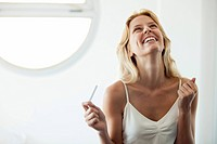 Young woman holding pregnancy test, laughing