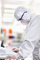 Engineer in clean suit taking notes in silicon wafer manufacturing laboratory