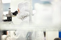 Scientist in clean suit examining silicon wafer under microscope in clean room laboratory