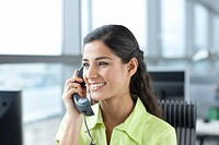 Smiling brunette receptionist talking on telephone in office