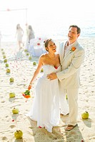 Bridal couple laughing on beach