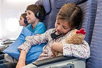 Girl sleeping on airplane holding stuffed toy