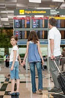 Family looking at arrival departure board in airport