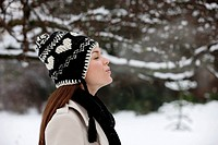 A young woman wearing a woolen hat, breathing into the cold air