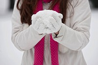 A young woman holding a handful of snow, close up