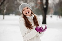 A young woman holding a handful of snow, laughing