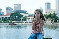 Girl eating ice cream cone by river