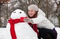 A young woman taking a photograph of a snowman on a mobile phone