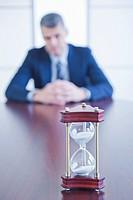 Hourglass on desk, businessman sitting on background
