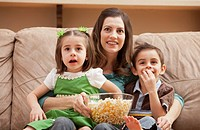 Front view of mother with children 4_5, 6_7 sitting on couch watching tv and eating popcorn