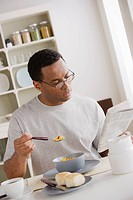 Mid adult man eating breakfast and reading newspaper