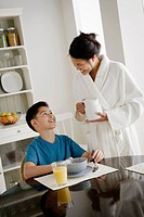 Mother serving breakfast to son