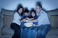 Family sitting on sofa and watching television