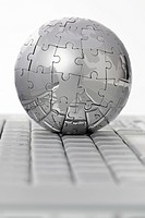 Metal puzzle globe on computer keyboard, on white background