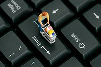Figurine with miniature shopping cart on a computer keyboard