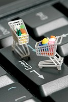 Miniature shopping carts on a computer keyboard