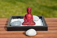 Red Buddha sits surrounded by stones and candles in the sun