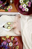 A young Caucasian woman lies on a massage table with a candle and flowers with a face mask on and cucumbers.
