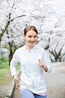 Beautiful teenage girl jogging in park with blooming apple trees