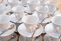 many empty tea cups on saucers with teaspoons