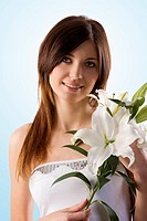 pretty and young sweet girl with dark hair and some lily near her face