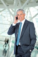 Smiling Businessman with one hand in pocket talking on cellphone with blurred people and building lobby in background