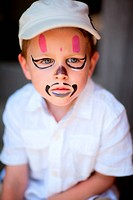 Small boy having his face painted as a pirate