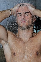 young good looking and attractive man with muscular body wet taking showr in bath with black tiles in background