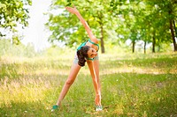 Young sporty lady doing aerobics or yoga outdoors in a forest. Sport and healthy life concept.