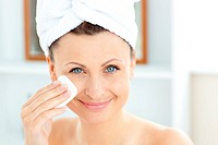 Joyful young woman with a towel putting cream on her face in the bathroom at home