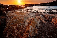 The sun can be seen setting over a rocky beach on the Pacific Coast