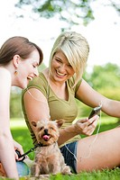 Young women with dog listening to music at a park