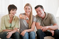 A group of three friends are sitting on a couch together and watching TV. They are smiling at the camera. Horizontally framed shot.