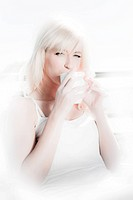 high key image of a beautiful blonde woman having coffee in a restaurant