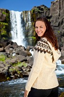 A beautiful Scandinavian woman wearing traditionally patterned knitwear smiling in front of a mountain waterfall. Shot on location in Iceland.