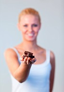 Young friendly woman holding chocolate and smiling at the camera with focus on chocolate