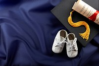 White baby shoes, cap, tassel and diploma shot on blue graduation gown with space for copy