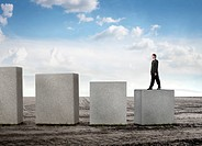 Businessman standing on the lower of some cubes