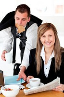 Delighted businesswoman with a cup smiling at the camera her boyfriend taking papers and rush
