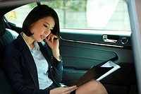 Businesswoman Using Laptop And Cell Phone In Car